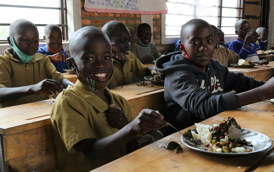 Donat, aged 9, enjoys a WFP-supplied school meal with classmates